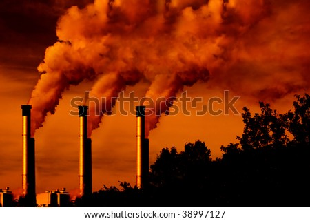factory smoke at sunset with shadow copy space - stock photo