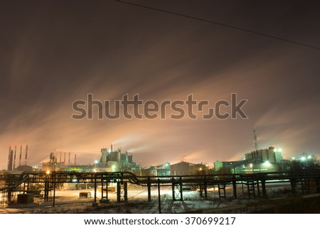 factory with a steam cloud blown by the wind in a cold starry winter night - stock photo