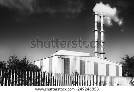 Factory with smoke from pipes - stock photo
