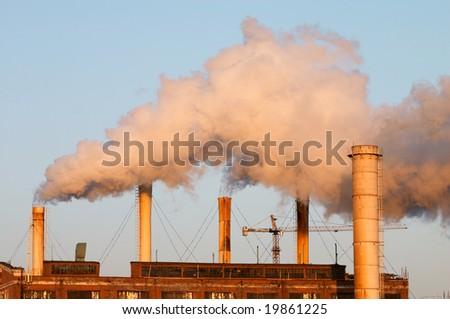 Factory with smokestacks doing air pollution - stock photo