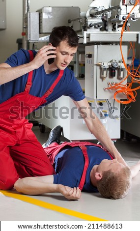 Factory worker calling for help after accident during work - stock photo