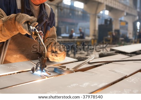 Factory worker cutting metal sheets using acetylene torch - stock photo