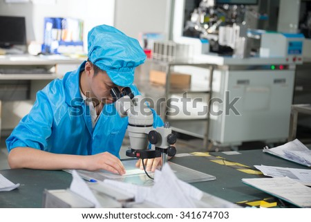 Factory worker in China looking through a microscope - stock photo