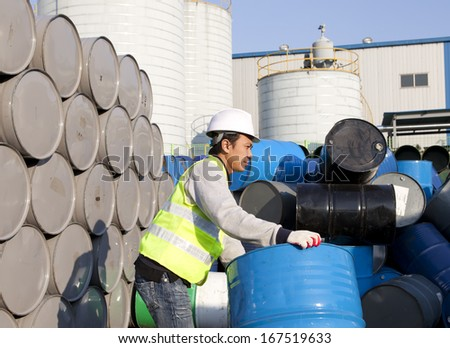 Factory worker moving a drum - stock photo
