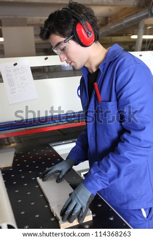 Factory worker wearing ear defenders - stock photo