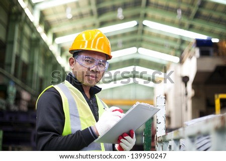 Factory worker with clipboard on the hand - stock photo