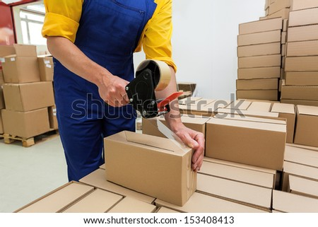 Factory worker with packing tape gun dispenser finishing a delivery - stock photo