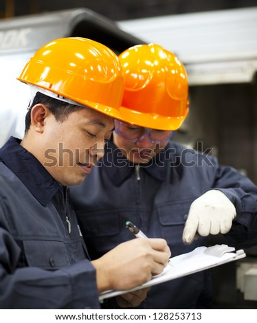 Factory workers discussion inspection report - stock photo