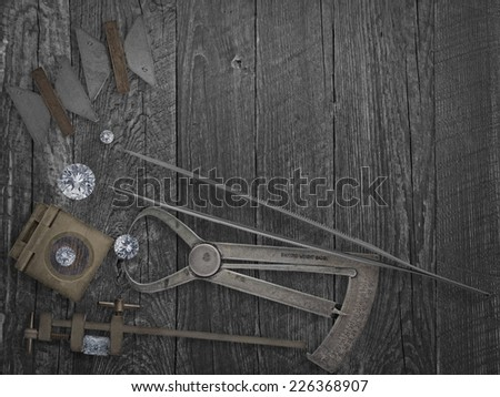 faded colors vintage jewelers tools and diamonds over wooden bench, space for text - stock photo
