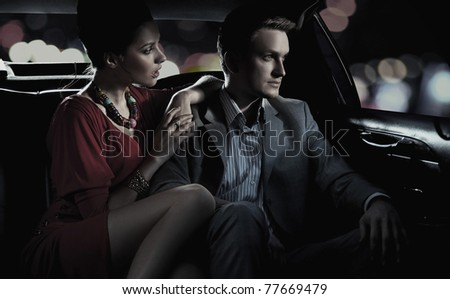 Faded image of beautiful couple sitting in a limousine - stock photo