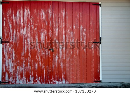 Faded red barn door with black latches on a white building - stock photo