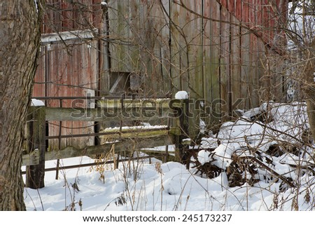 Fading red barn framed by the snow-covered fields of Western New York.  - stock photo