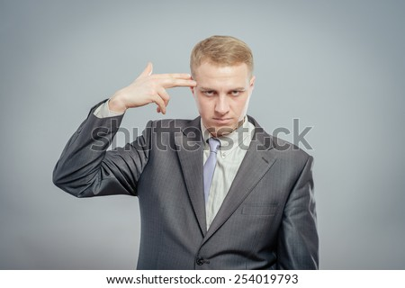 Failed again. Depressed young man in shirt and tie touching his temple with finger gun and looking at camera while standing isolated on gray - stock photo