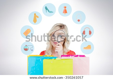 Fair-haired woman looking through a magnifying glass against gift bags - stock photo
