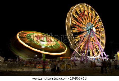 Fair rides at the state fair viewed at night with a long exposure. - stock photo
