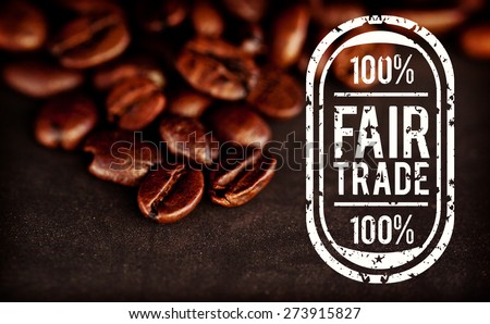 Fair Trade graphic against dark blurred coffee seeds laid out together on a black table - stock photo