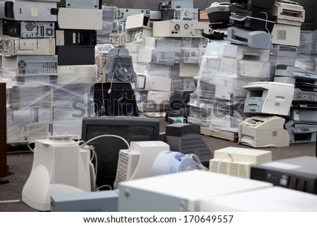 FAIRFAX, VA - DECEMBER 5: Many computers and printers to be recycled stacked at a dumpster on December 5, 2013 in Fairfax, VA. Components, plastic and metal will be separated and melted. - stock photo