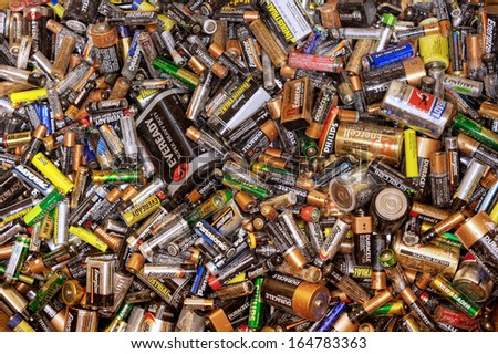 FAIRFAX, VA - NOVEMBER 21: Different types of used batteries lying in a heap at a recycling center on November 21, 2013 in Fairfax, VA. Types are AAA, AA, 9-volt and super heavy duty. - stock photo