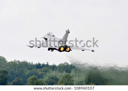 FAIRFORD, UK - JULY 8: french Air Force Rafale participates in the Royal International Air Tattoo airshow event July 8, 2012 near Cirencester, England. - stock photo
