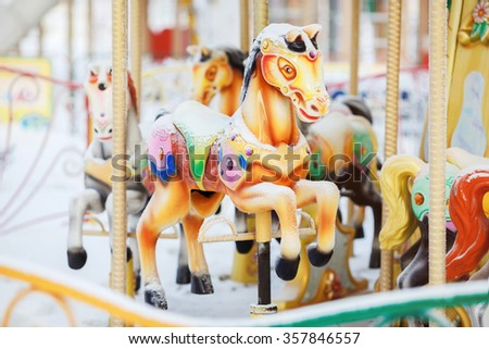 Fairground carousel horses during the day covered with snow in winter city park entertainment. Concept of abandoned amusement. - stock photo