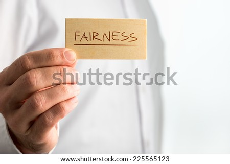 Fairness Concept Design- Close up Human Hand Holding Small Piece Wooden Sign with Underlined Fairness Text over White Shirt. - stock photo
