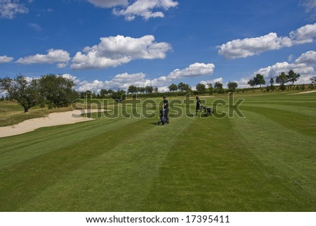 fairway of a beautiful golf course with golfers under dramatic summer sky - stock photo