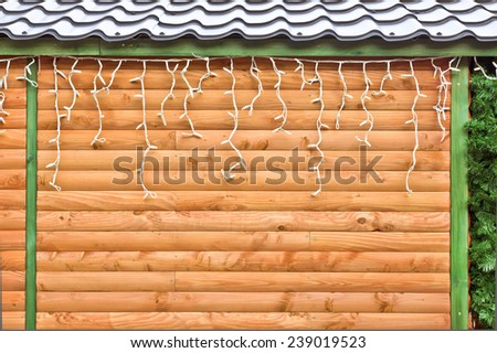 Fairy lights hanging on a wooden cabin - stock photo