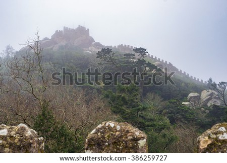 Fairy tale concept - moorish medieval castle fortress panorama with battlement - ancient stone walls and gear watchtowers during foggy day, Castle of the Moors ( Castelo dos Mouros ) Sintra, Portugal. - stock photo
