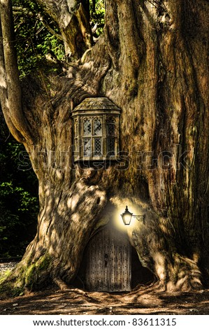 Fairytale fantasy house in tree trunk in forest - stock photo