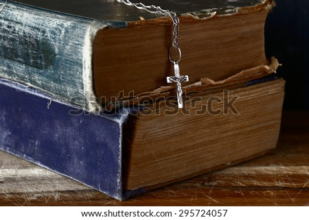 faith concept with close up of old bible and silver cross necklace - stock photo