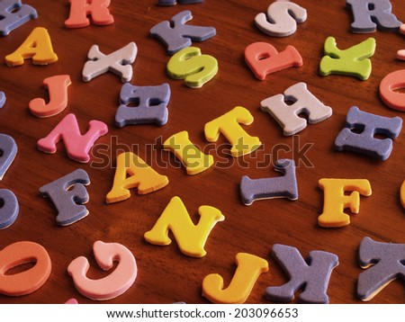 faith word written with toy letters over a dark wooden table    - stock photo