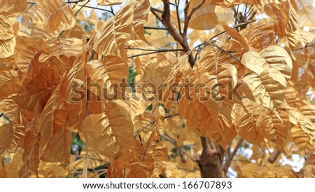 Fake golden leaves decorated on the tree - stock photo
