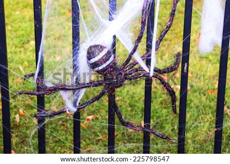 Fake spider on a metal fence - stock photo