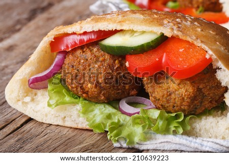 falafel with fresh vegetables in pita bread close-up on wooden table horizontal   - stock photo
