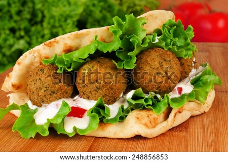 Falafel with vegetables and  tzatziki sauce in pita bread close-up on wooden table - stock photo