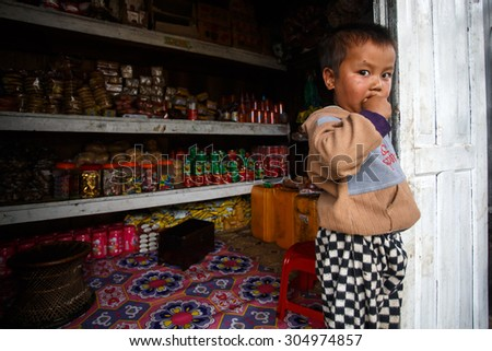 FALAM, MYANMAR - JUNE 17 2015: Local cute boy stands at convenience store entrance at the start of the monsoon season in the recently opened to tourists Chin State region of Western Myanmar (Burma) - stock photo