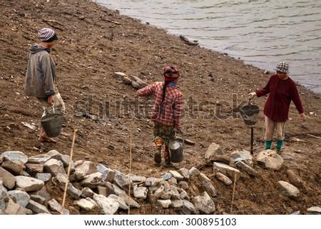 FALAM, MYANMAR - JUNE 17 2015: Local people work hard on construction at Laiva Dam in Chin State, Western Myanmar (Burma) - stock photo