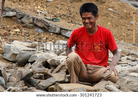 FALAM, MYANMAR - JUNE 17 2015: Local people work hard on construction at Laiva Dam in Chin State, Western Myanmar (Burma) - stock photo