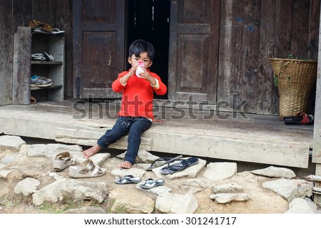 FALAM, MYANMAR - JUNE 17 2015: Small child sits on wooden hut step in recently opened region of Chin State in Western Myanmar (Burma) - stock photo