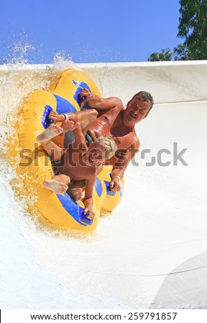 Faliraki,Rhodes, Greece-August 17,2014:Father and son drive with tube on the rafting slide in the  Water park.Rafting slide is one of many popular game for adults and children in Water park - stock photo