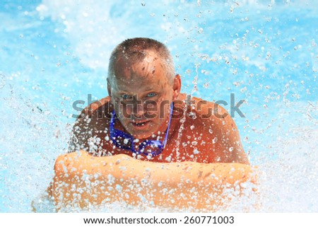 Faliraki,Rhodes,Greece-August,12,2015:Man on the mat racer slide in Water park,Mat racer slide is very popular for Youth and adults persons in the Water Park. - stock photo
