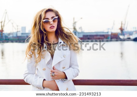 Fall autumn fashion portrait of elegant lady model posing at sea port in evening soft sunlight, wearing extravagant gold sunglasses and white cashmere stylish coat. - stock photo