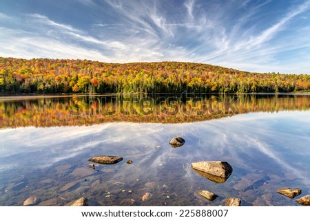 Fall colors and clouds reflected at the lake - stock photo