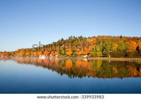 Fall Colors Reflected in Calm Lake - brilliant fall colors reflected in a glassy, smooth, blue lake.  Copy space on water and in sky if needed. - stock photo