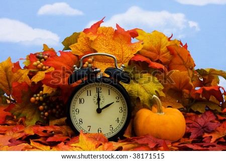 Fall coloured leaves with a black clock on a sky background, Fall Leaves - stock photo