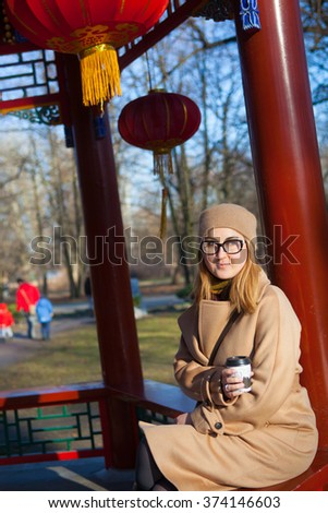 Fall concept - autumn woman drinking coffee on park bench under fall foliage. Beautiful young modern woman smiling happy and cheerful in coat. - stock photo