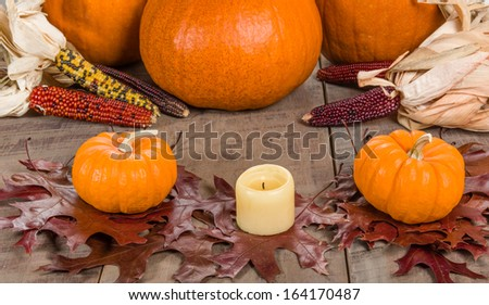 Fall decorative display with candle and pumpkins - stock photo
