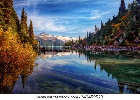 Fall foliage along calm mountain lake - stock photo