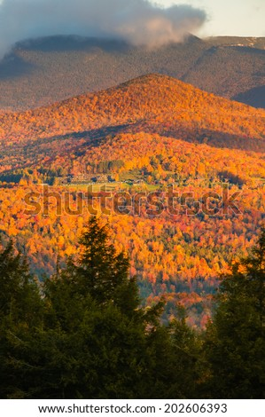 Fall foliage landscape with Trapp Family Lodge and Mt. Mansfield in the background, Stowe, Vermont, USA - stock photo