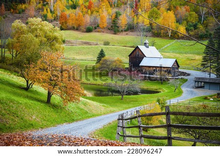Fall foliage, New England countryside at Woodstock, Vermont, farm in autumn landscape. Old wooden barn surrounded by colorful trees. - stock photo